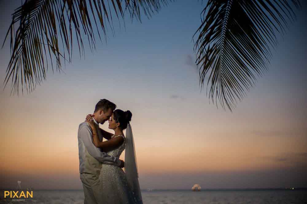 Cancun lagoon sunset wedding photo with palms and boat in the background