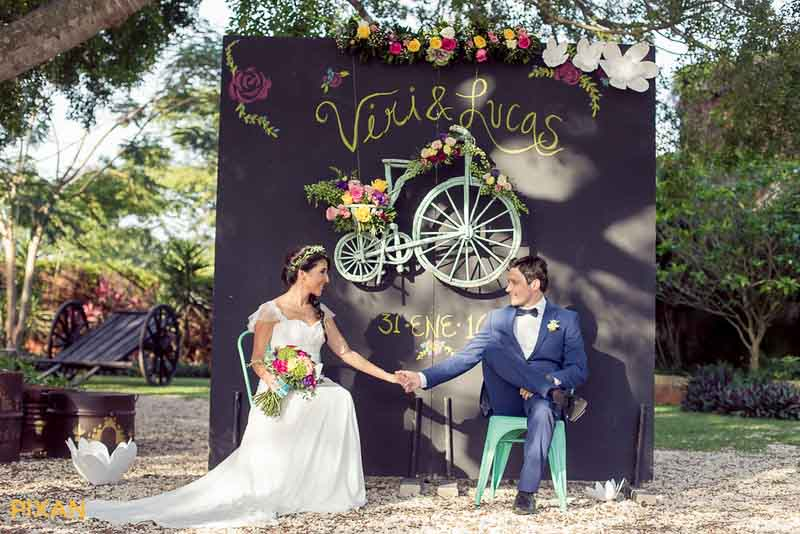 Chalkboard sign wedding backdrop with bicycle and flowers