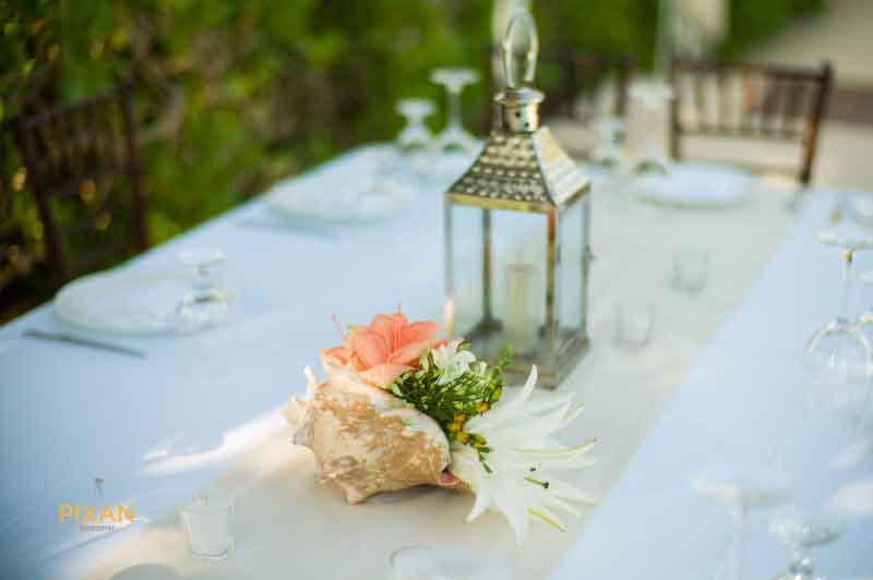 wedding table decoration featuring local flowers inside a shell found on the beach