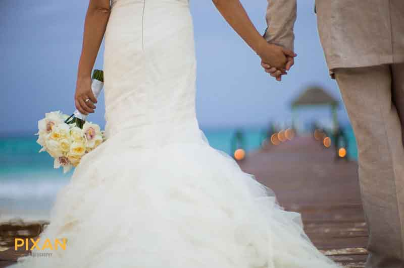 bridal couple holding hands on the pier at Viceroy Riviera Maya