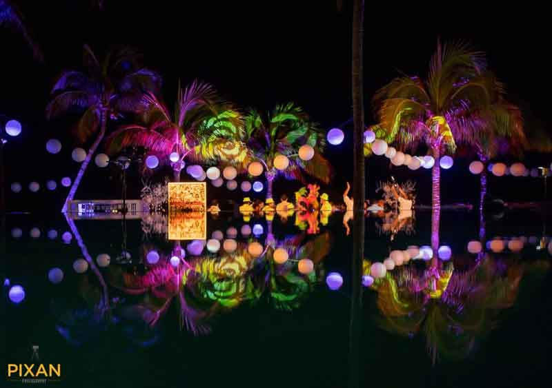 lights in the trees make for colorful beach wedding reception decoration