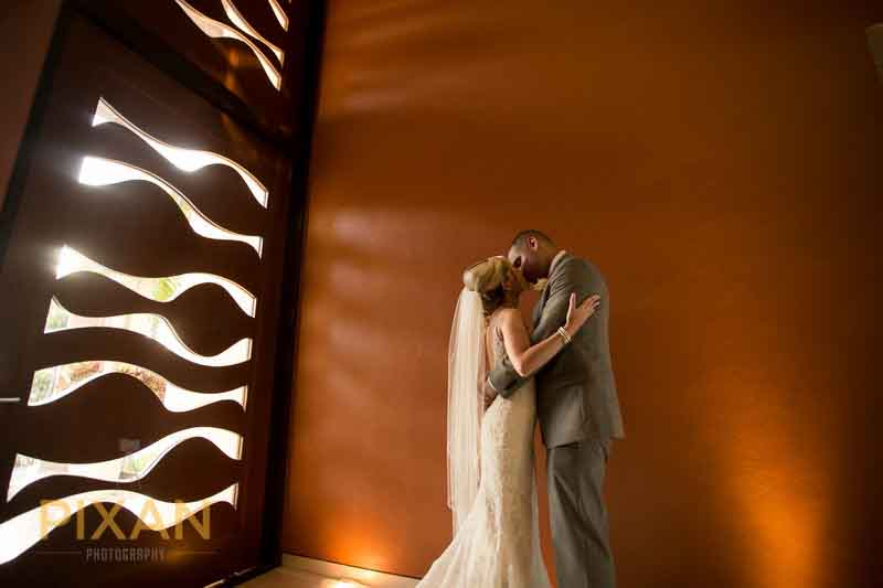 bridal couple with light streaming through patterned door