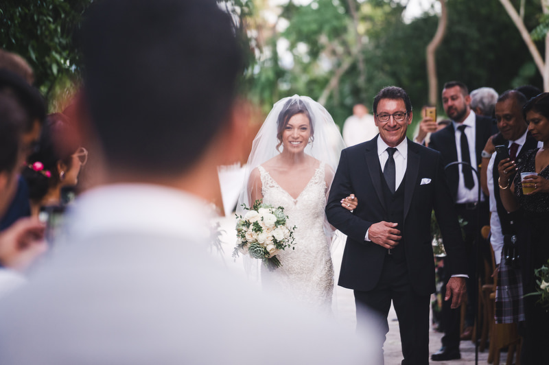 Hotel Xcaret Mexico Indian Mixed Destination Wedding ceremony christian bride walking down the aisle with her father