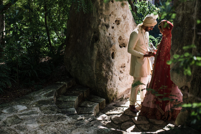 Hotel Xcaret Mexico Indian Mixed Destination Wedding groom looking at brides hands