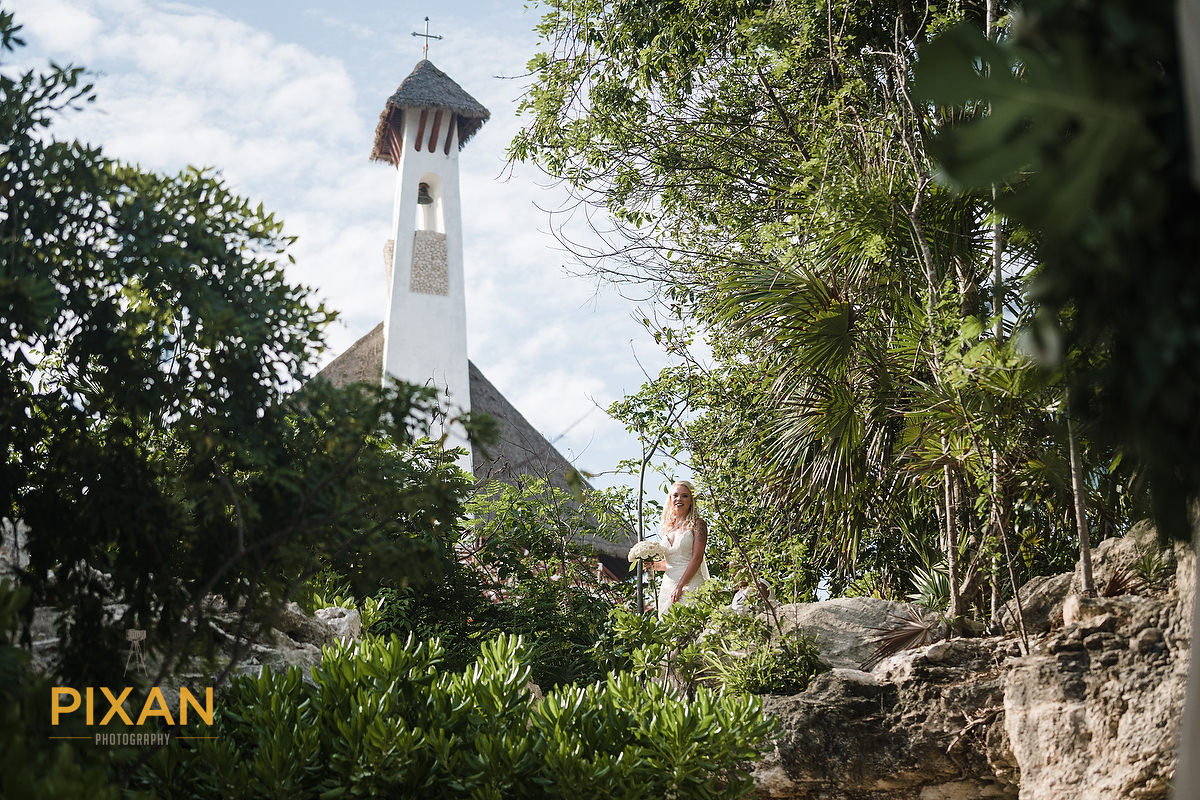 bride walking to her wedding ceremony at Cuevitas & Bar Cuevitas with Chapel in the background