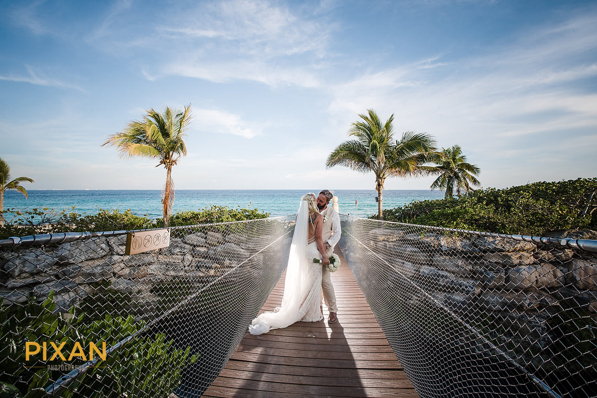 Hotel Xcaret bridal portrait on rope bridge over inlet on the way to the beach