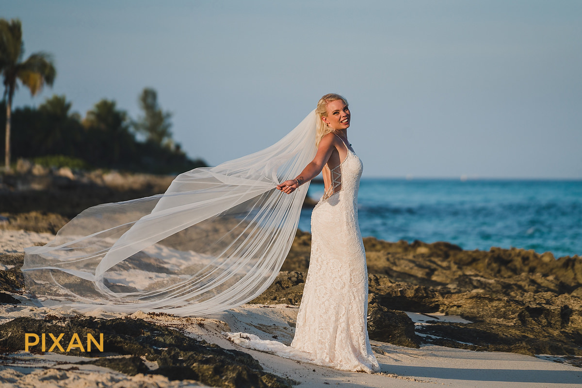Beach bridal portrait with vail flowing in sea breeze