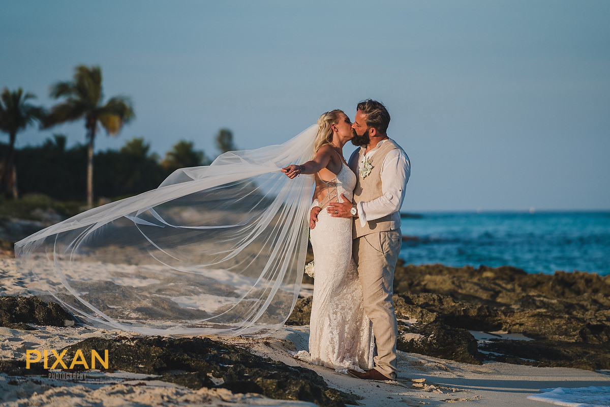 bridal kiss on the beach with vail flowing in the sea breeze