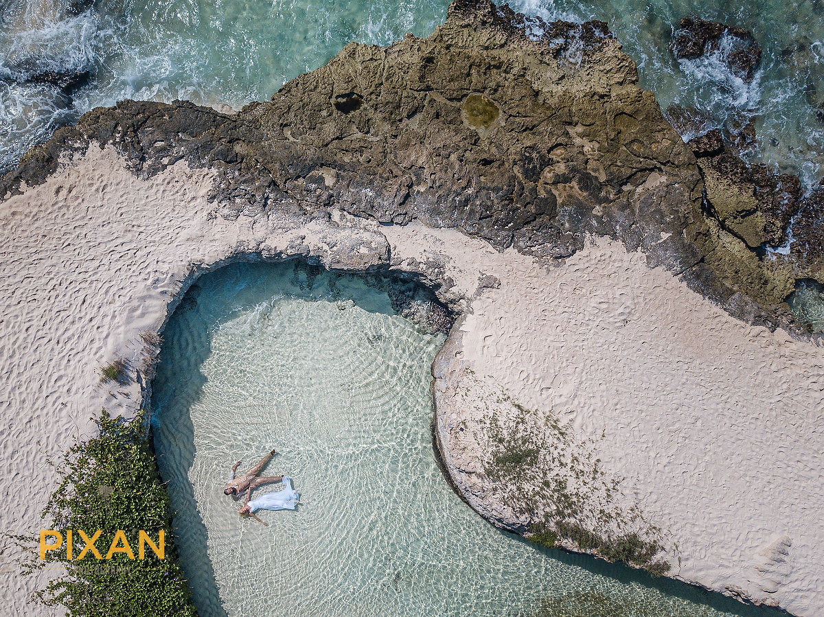birds eye view coastal bridal portrait in the sand, sea and inlet